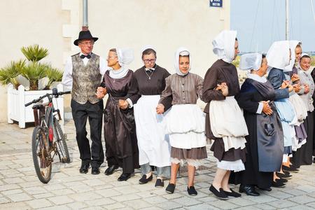 LE CROISIC, FRANCE - JULY 26, 2014: group amateurs in national dresses dancing folk breton dance outdoors in Le Croisic town, France. Le Croisic is town in western France on Atlantic coast