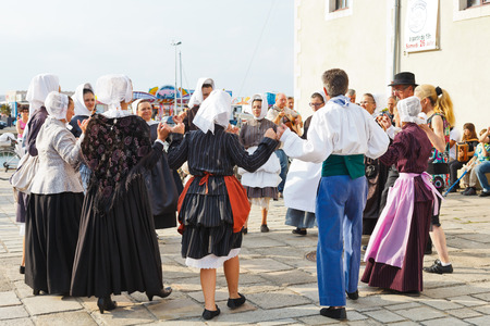 LE CROISIC, FRANCE - JULY 26, 2014: group amateurs in national costumes dancing traditional breton dance outdoors in Le Croisic town, France. Le Croisic is town in western France on Atlantic coast