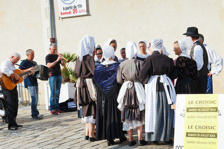 LE CROISIC, FRANCE - JULY 26, 2014: group amateurs in traditional dresses dancing folk breton dance outdoors in Le Croisic town, France. Le Croisic is town in western France on Atlantic coast