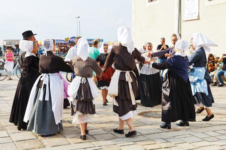 LE CROISIC, FRANCE - JULY 26, 2014: group amateurs in native dresses dancing folk breton dance outdoors in Le Croisic town, France. Le Croisic is town in western France on Atlantic coast