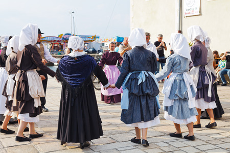 LE CROISIC, FRANCE - JULY 26, 2014: group amateurs in national dresses dancing traditional breton dance outdoors in Le Croisic town, France. Le Croisic is town in western France on Atlantic coast