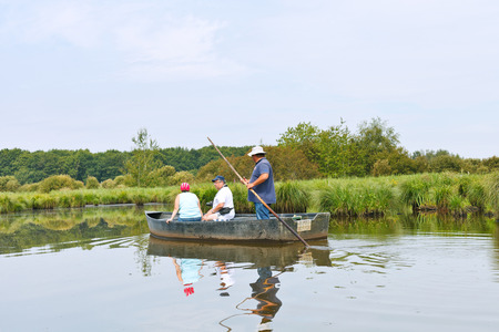 parc naturel: BRIERE, FRANCE - JULY 27, 2014: tourists floating in boat in marsh in Briere Regional Natural Park. The park includes the largest wetland area in France, it covers around 100,000 acres
