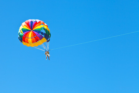 kiting: people parascending on parachute in blue sky in summer day