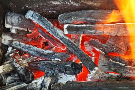 woodburning: flame over hot wood-burning coals close up