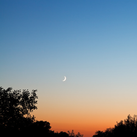 late summer: new moon in dark blue and red sky at late sunset in summer Stock Photo