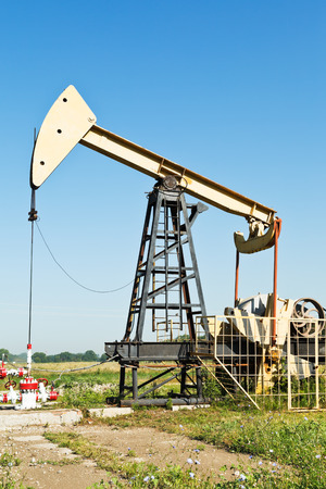 beam pump: view of pumpjack pumping oil in summer day Stock Photo