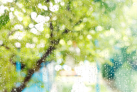 rainy season: wet home window with raindrops after summer rain