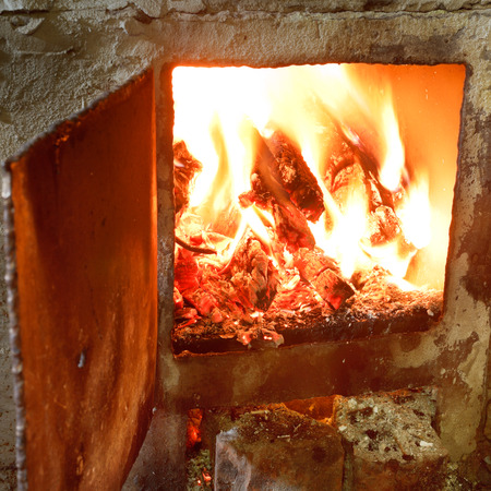 burning wood in furnace with open door close up photo