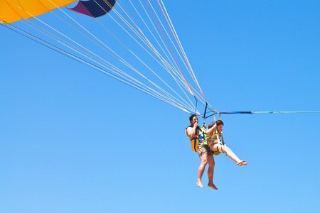 man and girl parasailing on parachute in blue sky in summer day photo