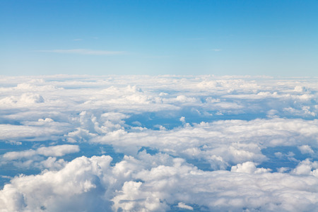 horizon above white clouds in blue sky and lands under clouds photo