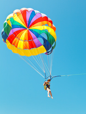 parasailing: girl parascending on parachute in blue sky in summer day Stock Photo