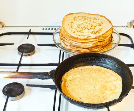 baked pancake in pan and stack of prepared pancakes photo