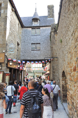 mount saint michael: MONT SAINT-MICHEL, FRANCE - AUGUST 9, 2014: tourists in Mont Saint-Michel abbey. One of French recognisable landmarks, Mont Saint-Michel and its bay are in UNESCO list of World Heritage Sites