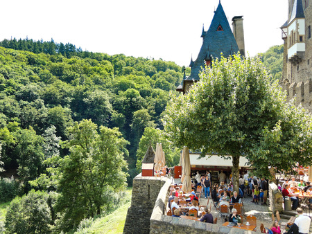 family owned: BURG ELTZ, GERMANY - AUGUST 12, 2014: tourists in Castle Eltz above Mosel river, Germany. The castle is still owned by a branch of same family that lived there in the 12th century, 33 generations ago