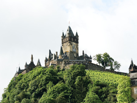 mention: COCHEM, GERMANY - AUGUST 14, 2014: Cochem Imperial castle (Reichsburg Cochem) on green hill in Germany. The Reichsburg Cochem had its first documentary mention in 1130.