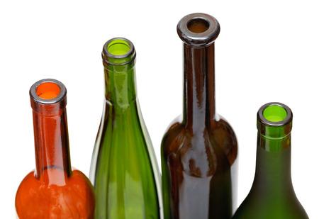 amber coloured: bottlenecks of few colored wine bottles close up isolated on white background