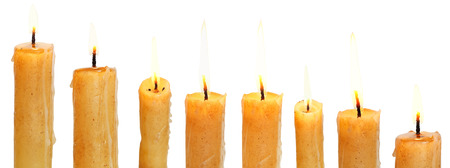 lit collection: set of lighted candles close up isolated on white background