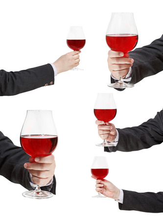 proposing a toast: set of red wine glass in businessman hand isolated on white background Stock Photo
