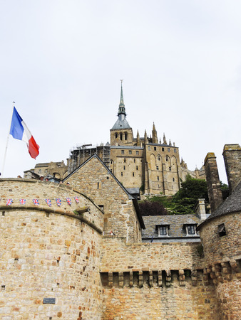 mount saint michael: flag, stone walls and abbey mont saint-michel in Normandy, France