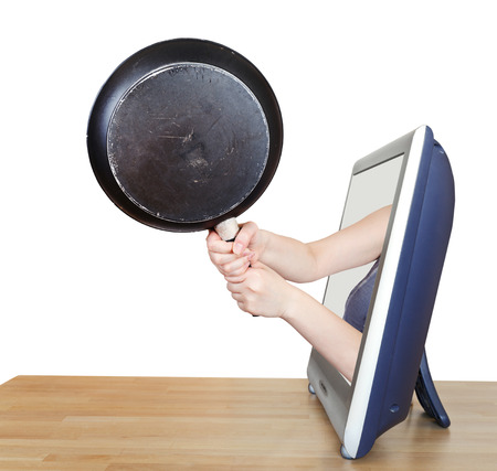black skillet in female hands leans out TV screen isolated on white background photo