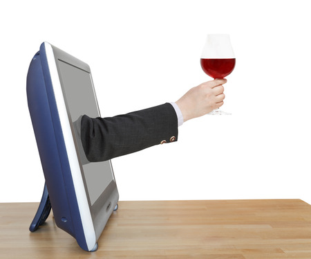 proposing a toast: red wine glass in businessman hand leans out TV screen isolated on white background Stock Photo