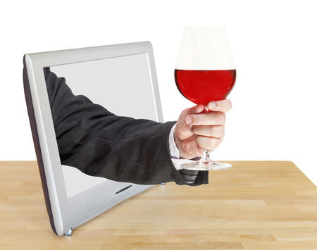 proposing a toast: red wine glass in male hand leans out TV screen isolated on white background