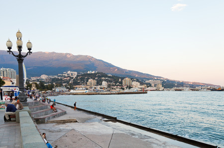 crimean: YALTA, RUSSIA - SEPTEMBER 28, 2014: tourists on waterfront in Yalta city in evening . Yalta is resort city on the north coast of the Black Sea on the Crimean peninsula.