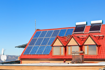 modern energy-saving technology - Solar Batteries and heaters on house roof