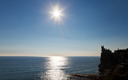 sun over Black Sea and Aurora cliff with Swallows Nest castle on Southern Coast of Crimea