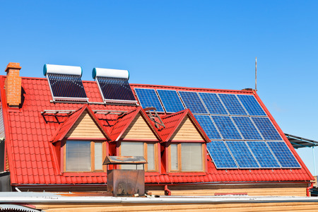 contemporary energy-saving technology - Solar Batteries and heaters on home roof photo