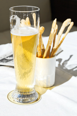 beerhouse: glass of beer and bread sticks on table at outdoor restaurant Stock Photo