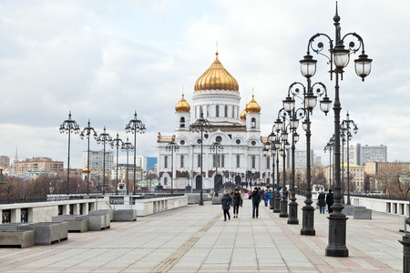 MOSCOW, RUSSIA - NOVEMBER 2, 2014: people on Patriarshy bridge to Cathedral of Christ the Saviour in Moscow. Modern church building was completed in 1999 and footbridge was constructed in 2003-2004.