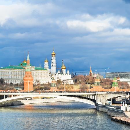 sun illuminated Bolshoy Kamenny bridge, Moskva River and Moscow Kremlin in autumn day photo