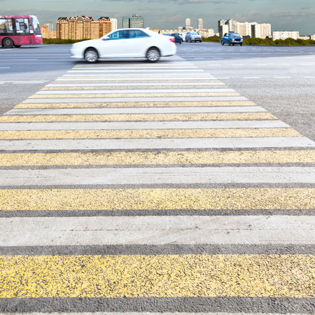 yellow and white crossing zebra of pedestrian crosswalk on urban street photo