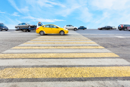 cab at yellow and white crossing zebra of pedestrian crosswalk on road photo