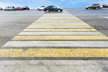 yellow and white crossing zebra of pedestrian crosswalk on road photo
