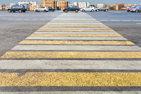 yellow and white pedestrian crossing on urban street photo