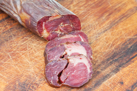 horse meat: sliced horse meat sausage kazi close up on cutting wooden board Stock Photo