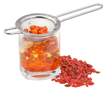 cooking of goji berry tincture - strainer in glass with goji berries infusion and handful of dried fruits isolated on white background