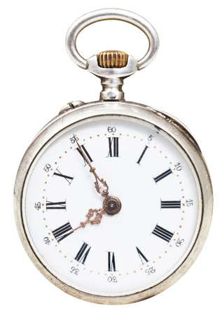 reveille: five minutes to eight oclock on the dial of retro pocket watch isolated on white background