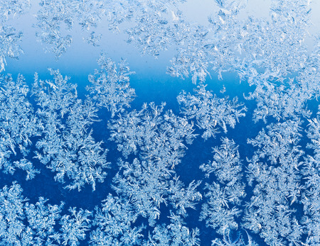 frozen snowflakes on window glass close up at blue winter sunrise photo