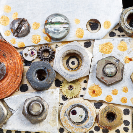 abstract background from bolts, screws, nuts on board close up photo
