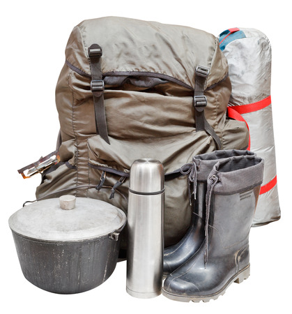 set of camping equipment with backpack, tent, pot, rubber boots, thermos, gas burner isolated on white background photo