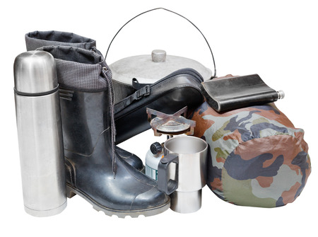 primus: set of camping belongings with gumboots, pot, thermos, flask, can, sleeping bag, gas burner isolated on white background Stock Photo