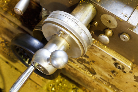 turning operation: scale handle of carriage of metal lathe machine in turning workshop
