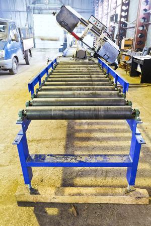 conveyor rail: roller feeder of cutting saw machine in mechanical workshop Stock Photo