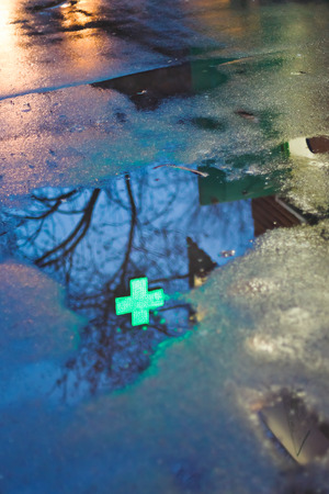 cross street with care: pharmacy cross reflection in rain puddle in dark urban evening Stock Photo