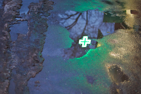 green cross reflection in rain puddle in dark urban evening Stock Photo