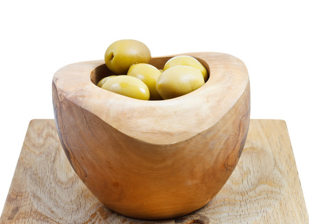 green olives in wooden bowl on board isolated on white background photo
