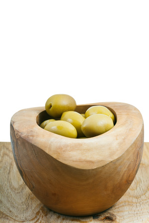 green olives in bowl on wooden plate close up isolated on white background photo
